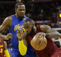 Cleveland Cavaliers' LeBron James (23) drives past Golden State Warriors' Kevin Durant (35) in the first half of an NBA basketball game, Sunday, Dec. 25, 2016, in Cleveland. (AP Photo/Tony Dejak)